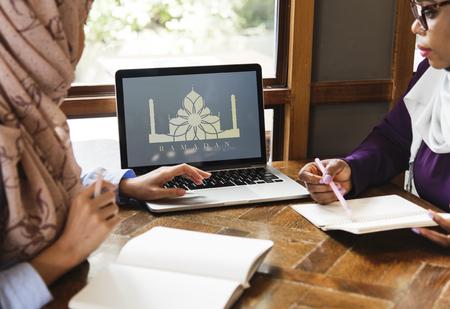 Muslim friends doing homework on a laptop