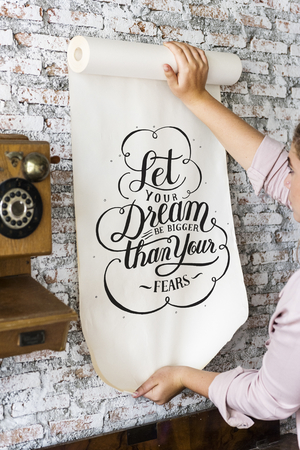 A woman holding a poster with motivation quote