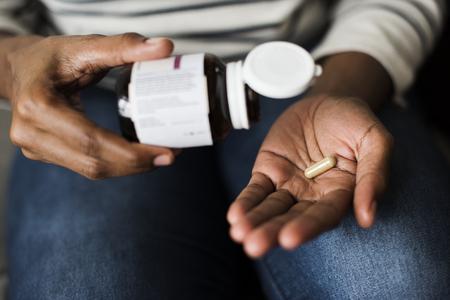 Mujer tomando pastillas para su salud Foto de archivo