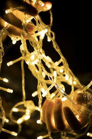 Hands holding garland decoration lights