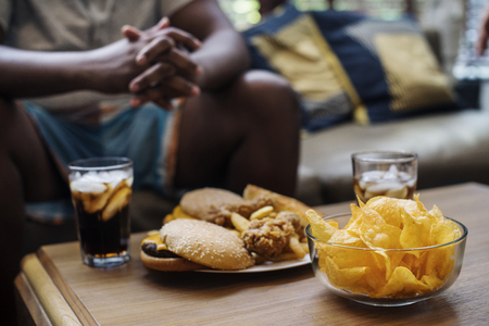 Fast food on a sofa table Stock Photo