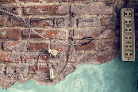 Power plug hanging on a brick wall Stock Photo