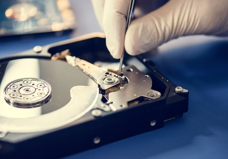 Closeup of hands with tweezers and computer hard disk Standard-Bild