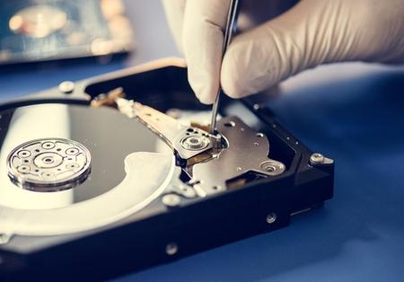 Primer plano de manos con pinzas y disco duro de computadora