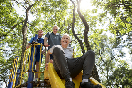 Senior men playing at a playground slide