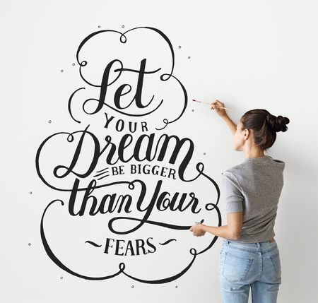 Female artist writing a life motivation quote on the wall Stock fotó - 109991412
