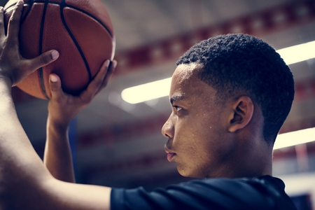 African American teenage boy concentrated on playing basketball Stock Photo