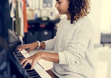 Woman playing on a piano Stock Photo