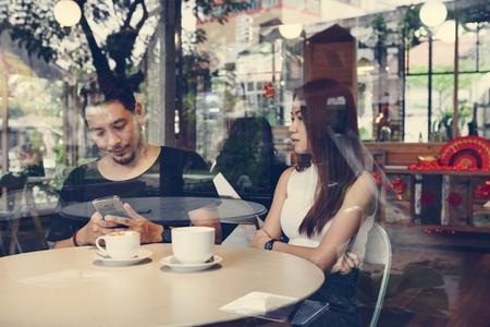 Pareja usando un teléfono en un café