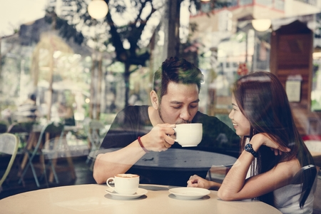 Lovely asian couple having coffee Фото со стока - 109991921