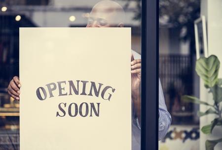 Uomo che mette sul segno di apertura del negozio presto
