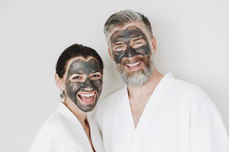 Happy couple wearing a charcoal mask Stockfoto