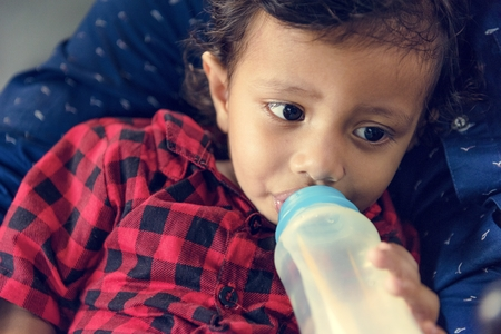 Young Indian boy drinking milk from bottle