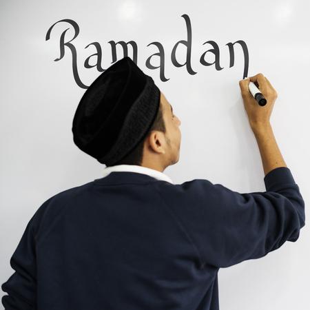 Young Muslim man writing ramadan on a whiteboard Stock Photo