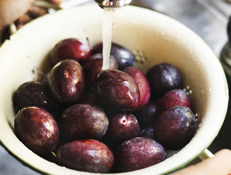 Organic plums being washed under running water food photography recipe idea