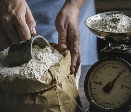 Baker weighing flour on a scale
