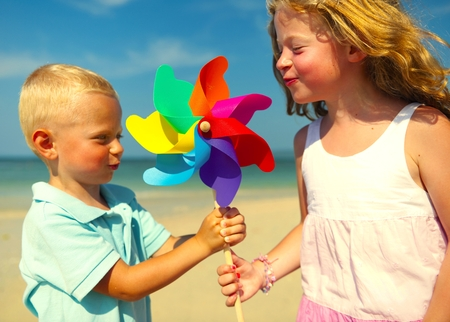 Brother and sister playing with a pinwheel Stock Photo