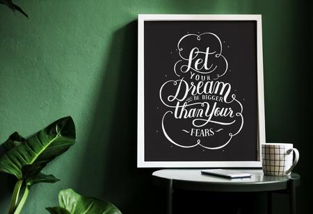 Ein Motivations-Typografiedruck auf dem Schreibtisch gegen die grüne Wand Standard-Bild