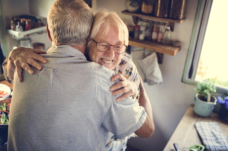Senior couple hugging in the kitchen