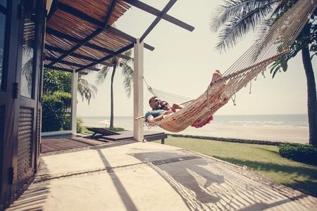 Couple relaxing in a hammock by the beach 版權商用圖片