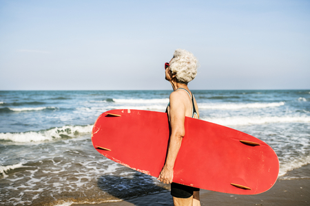 Senior woman holding a surfboard