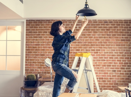 Woman changing lightbulb Standard-Bild - 111752716