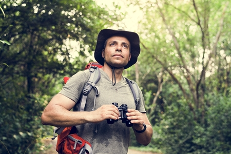 Man holding binoculars in the forest 写真素材