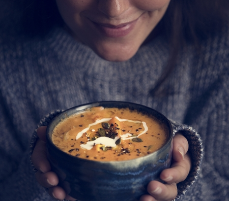 Woman holding a bowl of soup food photography recipe idea 写真素材