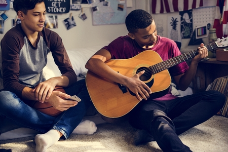 Teenage boys hanging out in a bedroom playing an acoustic guitar hobby and music concept Archivio Fotografico