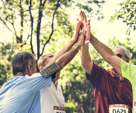 Group of senior athletes giving a high five Standard-Bild