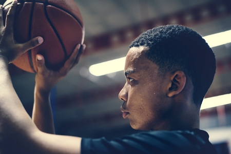 African American teenage boy concentrated on playing basketball Stockfoto