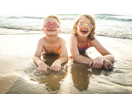 Petit frère et soeur s'amusant sur la plage
