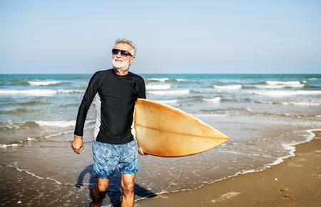 Un hombre mayor con una tabla de surf.