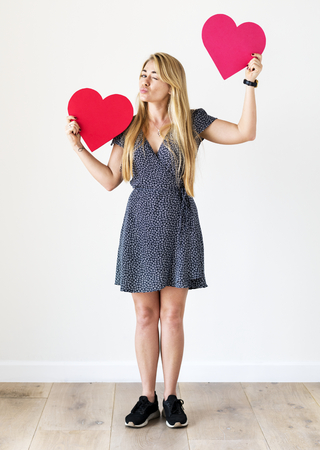 Happy Caucasian woman holding red hearts love and relationship concept