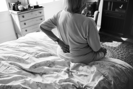 Black and white photo of a senior woman sitting on the bed in pain Standard-Bild - 111791882