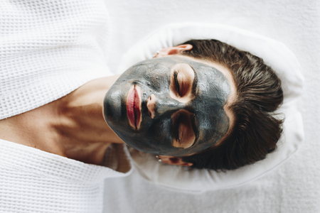 Woman relaxing with a charcoal facial mask Stock fotó - 110005362