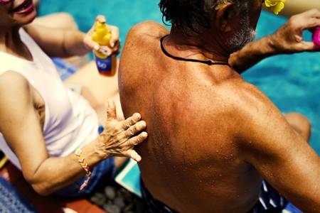 Wife putting on sunscreen on husbands back Stock Photo