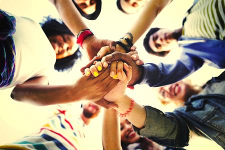 Diverse vrienden stapelen handen in eenheid