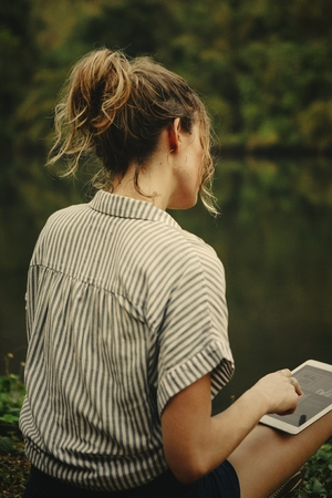 Woman alone in nature using a digital tablet