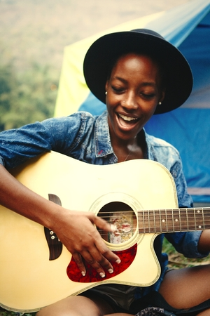 Woman playing guitar at a campsite Banque d'images - 110094635
