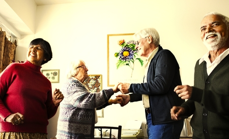Senior friends dancing together in the home