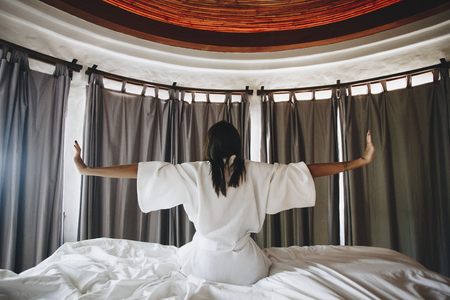 Woman waking up in a hotel room