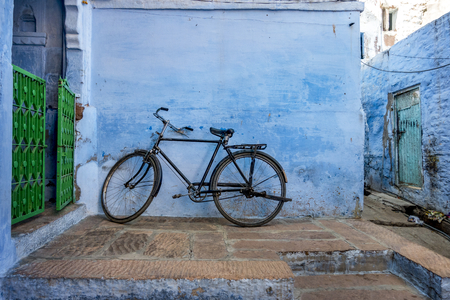 Bicycle leaning on the blue wall Stock Photo