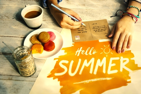 Woman writing a postcard in the summer