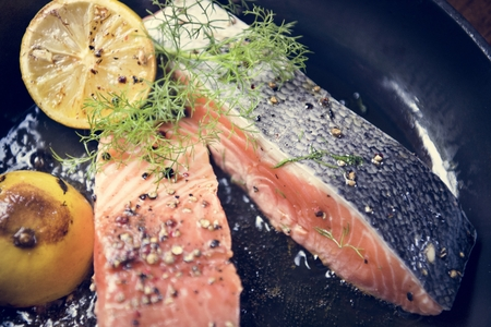 Grilled salmon fillet being sprinkled with salt and pepper Stock Photo