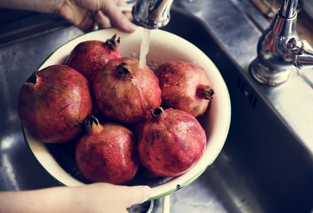A person washing pomegranate under running water food photography idea