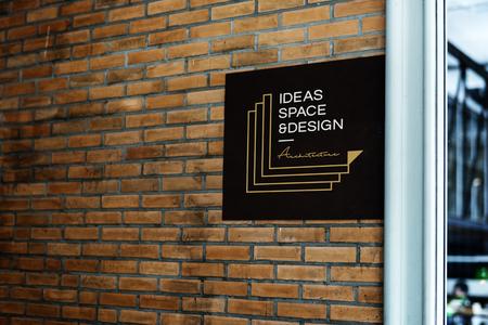 Square black sign on a brick wall mockup Фото со стока