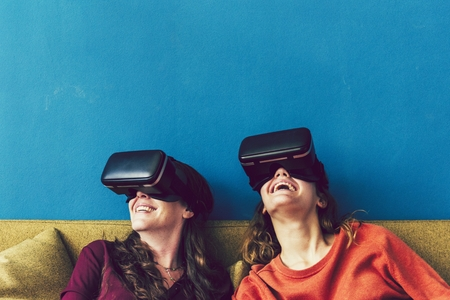 Two women using VR on a sofa Stock Photo