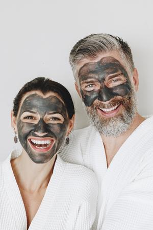 Happy couple wearing a charcoal mask Reklamní fotografie