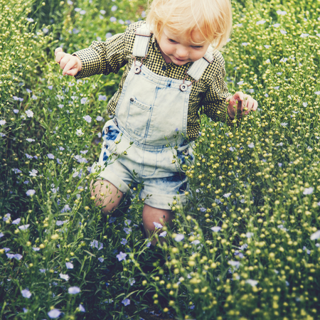 Boy playing in a field of flowers Stockfoto